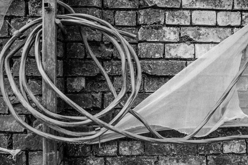 Schwarzweiss-Foto mit einer defekten Backsteinmauer, einem gedrehten Draht und einem Stoff stockbild
