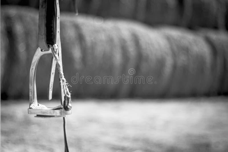 Schwarzweiss-Foto, schließen herauf Pferdesteigbügel in den Hintergrundheuschobern stockbild