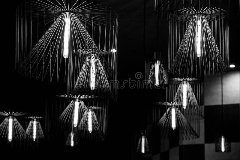 Schwarzweiss-Foto von den Drahtleuchtern gehangen von der Decke stockbilder