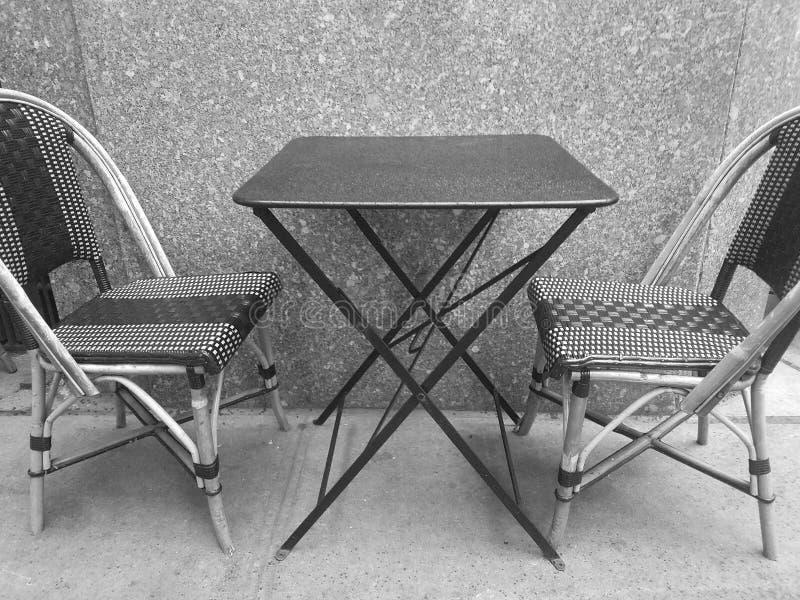 Schwarzweiss-Foto von zwei Caféstühlen und -tabelle draußen lizenzfreies stockfoto