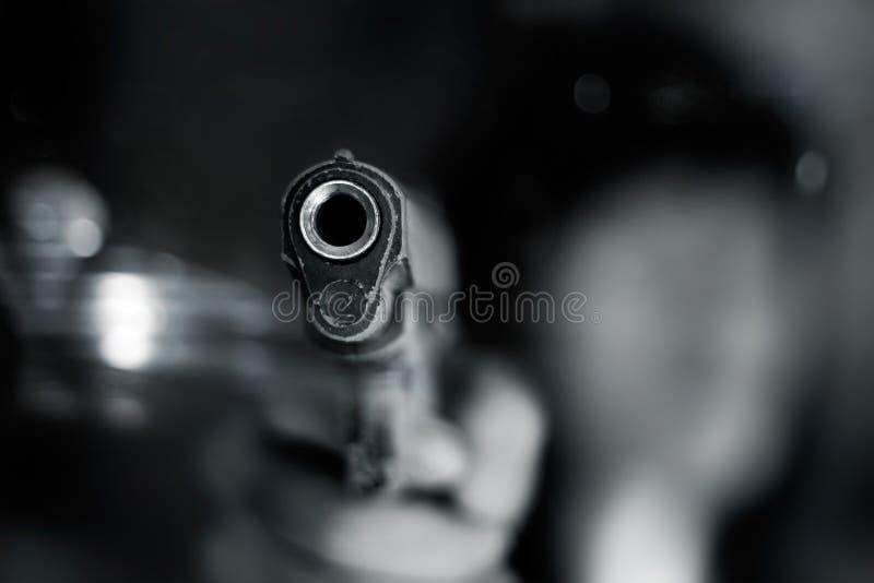 Schwarzweiss, Frau, die ein altes Gewehr auf Front mit einer Hand zeigt stockbilder