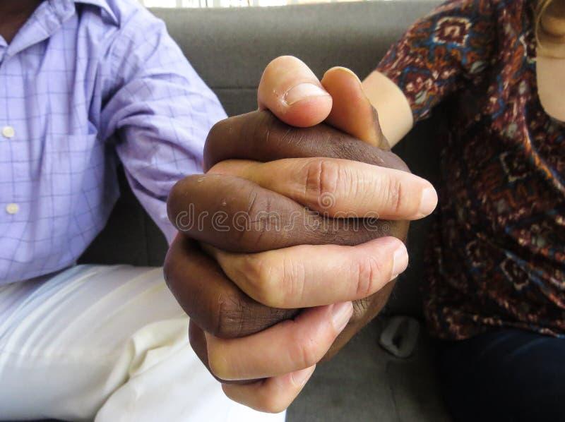 Schwarzweiss-Hände, die zusammen Teamwork und Verschiedenartigkeit zeigen stockbild