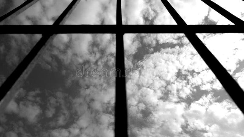 Schwarzweiss-Himmel und Wolke durch Schattenbildfensterrahmen lizenzfreie stockfotografie
