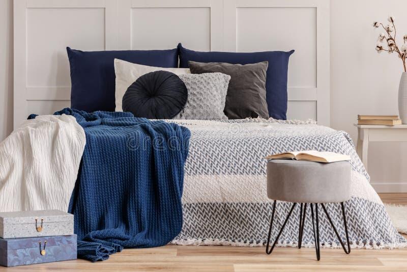 Schwarzweiss-Kissen auf gem?tlichem Bett im modernen Schlafzimmerinnenraum lizenzfreies stockfoto