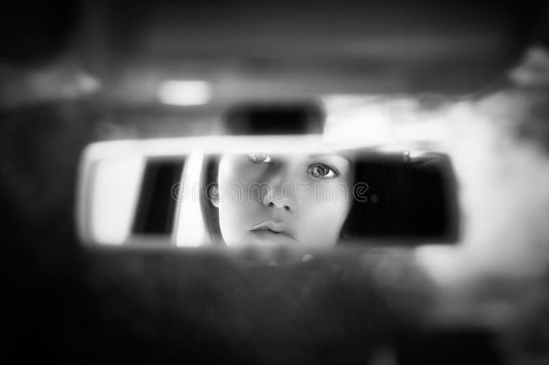 Schwarzweiss-Kunstbild des schönen Gesichtes der jungen Frau im Autorückspiegel stockbild