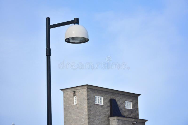 Schwarzweiss-Metalllampe und ein Gebäude gegen Hintergrund des blauen Himmels lizenzfreies stockfoto