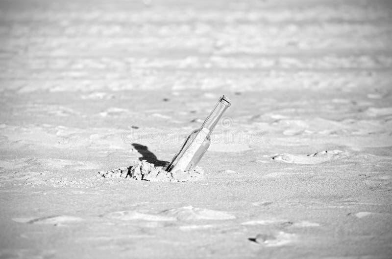 Schwarzweiss-Mitteilung in einer Flasche auf Sand, flache Tiefe von FI lizenzfreies stockbild