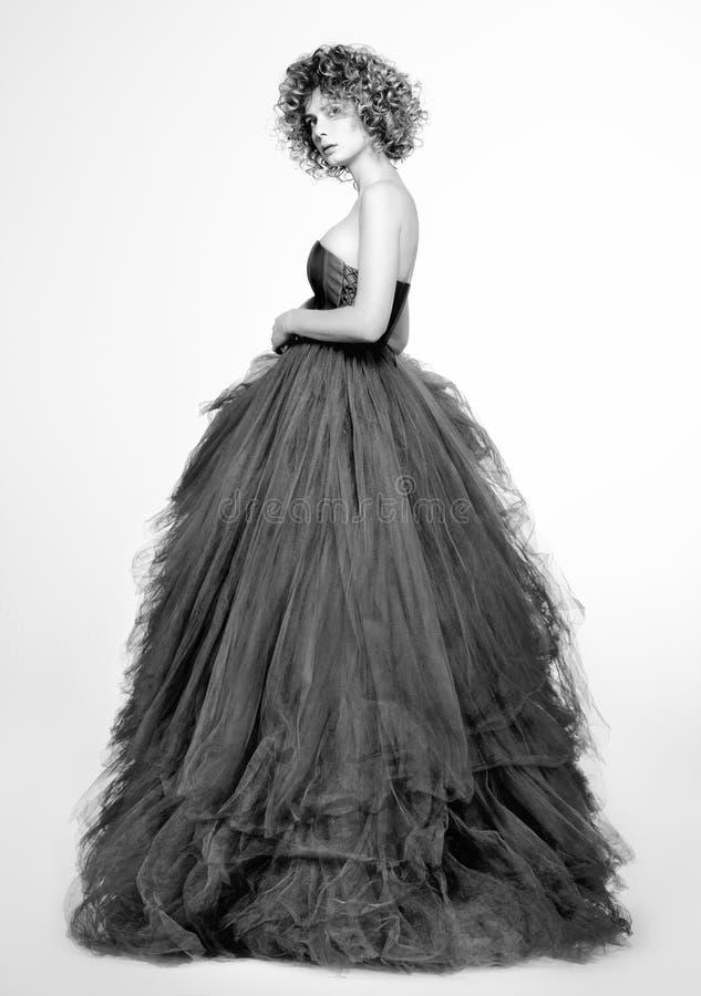 Schwarzweiss-Modeporträt der schönen jungen Frau in einem langen grauen Kleid stockfoto