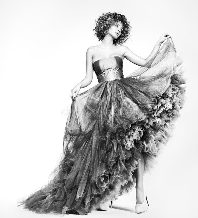 Schwarzweiss-Modeporträt einer jungen Frau in einem schönen Kleid lizenzfreies stockbild