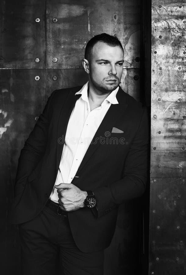 Schwarzweiss-Modeporträt eines reichen überzeugten und erfolgreichen Mannes, der einen klassischen Anzug trägt lizenzfreie stockfotos