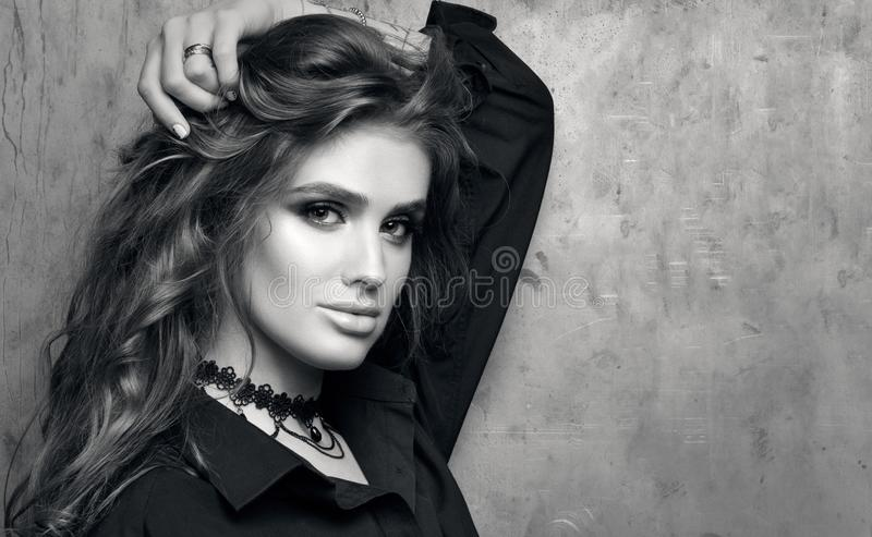 Schwarzweiss-Nahaufnahmeporträt der jungen Schönheit im schwarzen Hemd, das vor einer Metallwand aufwirft stockbilder