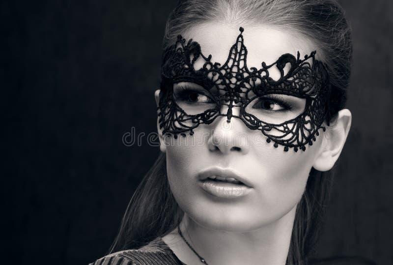 Schwarzweiss-Nahaufnahmeporträt einer schönen jungen Frau in der schwarzen Spitzemaske auf den Augen stockbild