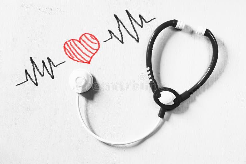 Schwarzweiss--phot des Spielzeugstethoskops und der bunten Herzschlagillustration über strukturiertem Hintergrund stockbilder