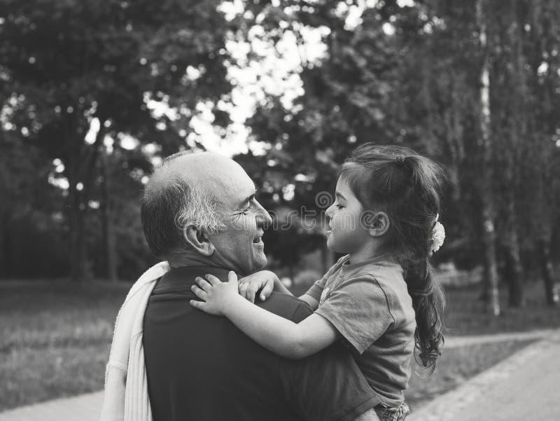 Schwarzweiss-Porträt des glücklichen Großvaters und des grandaughter, die am Park spielt lizenzfreies stockfoto