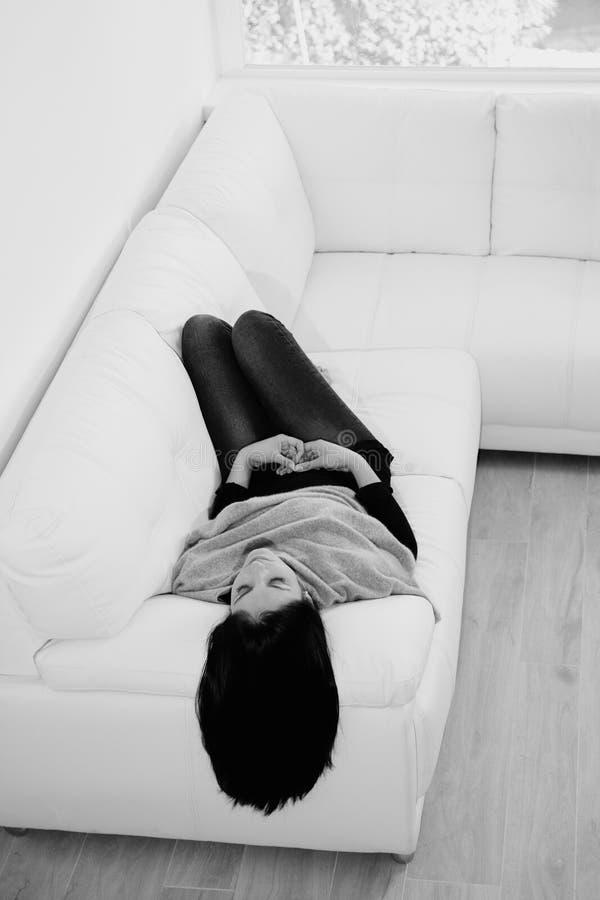 Schwarzweiss-Porträt der netten Schönheit liegend auf der lächelnden Entspannung des Sofas stockbilder