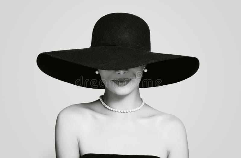 Schwarzweiss-Porträt der Weinlesefrau im klassischen Hut und im Perlenschmuck, Retro- anredendes Mädchen lizenzfreies stockbild