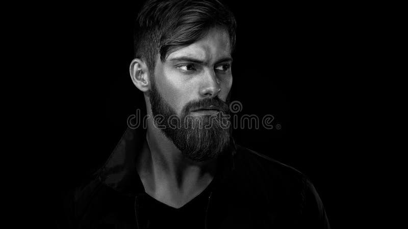 Schwarzweiss-Porträt des bärtigen gutaussehenden Mannes in einem nachdenklichen MO stockfotos
