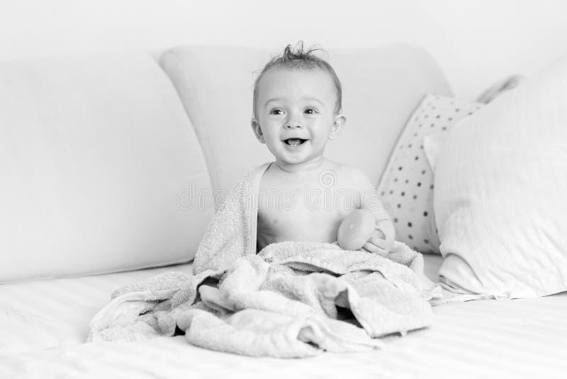Schwarzweiss-Porträt des lachenden Babys sitzend auf Bett nach h stockfoto