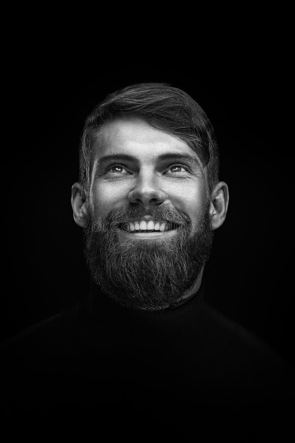 Schwarzweiss-Porträt des Lachens des jungen bärtigen Mannes lizenzfreies stockfoto