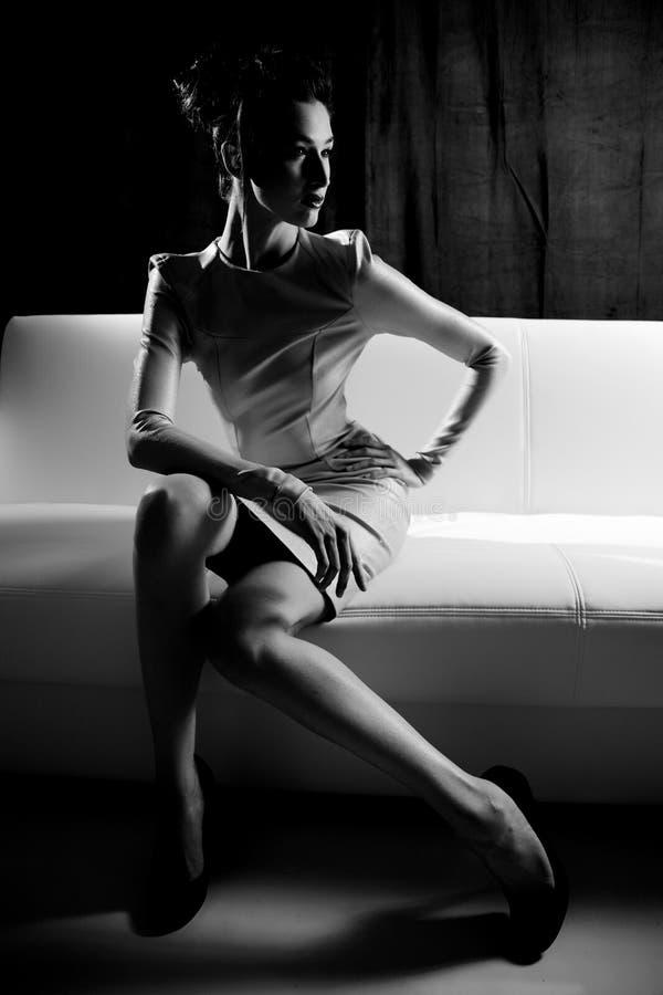 Schwarzweiss-Porträt des weiblichen Modells der Mode, das auf weißer Couch sitzt stockbilder