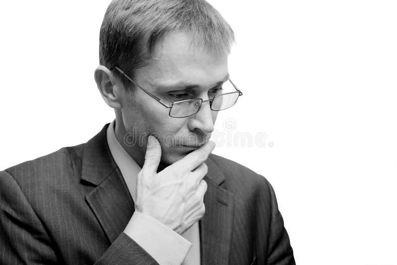 Schwarzweiss-Porträt eines Mannes in den Gläsern mit einem nachdenklichen Blick lizenzfreies stockbild