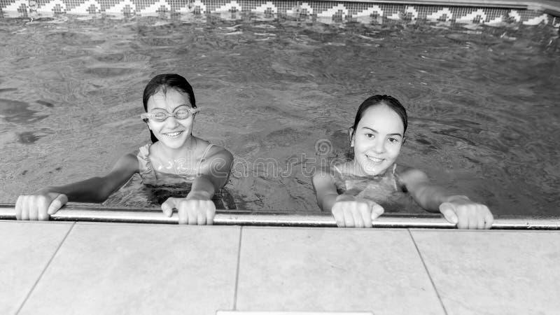 Schwarzweiss-Porträt von zwei glücklichen lächelnden Jugendlichen, die in zuhause Swimmingpool aufwerfen lizenzfreies stockbild