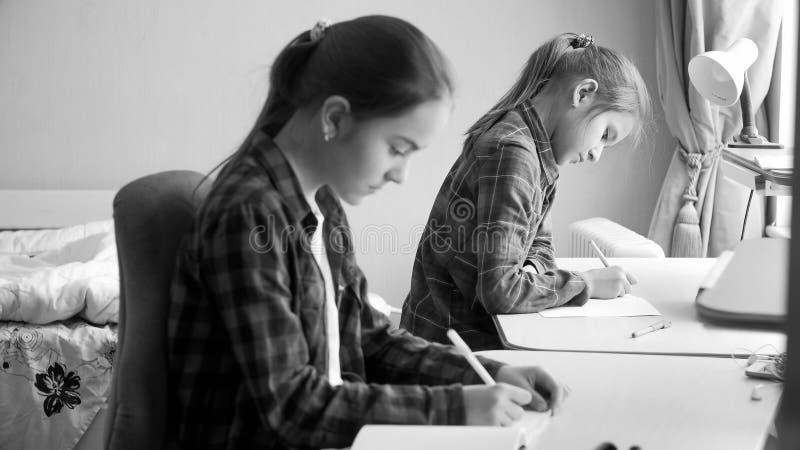 Schwarzweiss-Porträt von zwei Jugendlichen, die Hausarbeit im Schlafzimmer tun stockbild