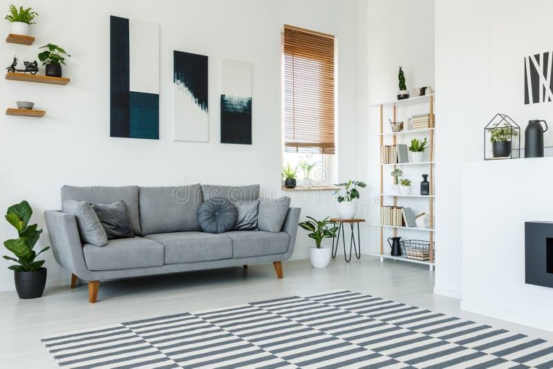 Schwarzweiss-Poster über grauer Couch im Wohnzimmerinnenraum stockfoto