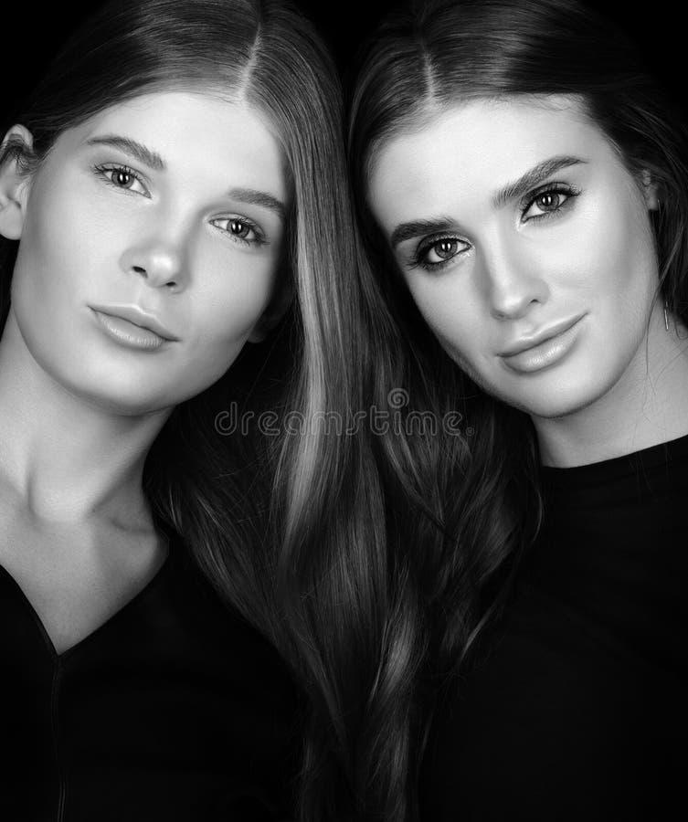 Schwarzweiss-Schönheitsporträtnahaufnahme Zwei schöne junge Frauen mit dem gesponnenen Haar lizenzfreie stockfotografie
