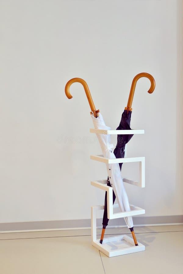 Schwarzweiss-Schirmständer in einem speziellen geometrischen Stand gegen weiße Wand im Raum stockfotografie