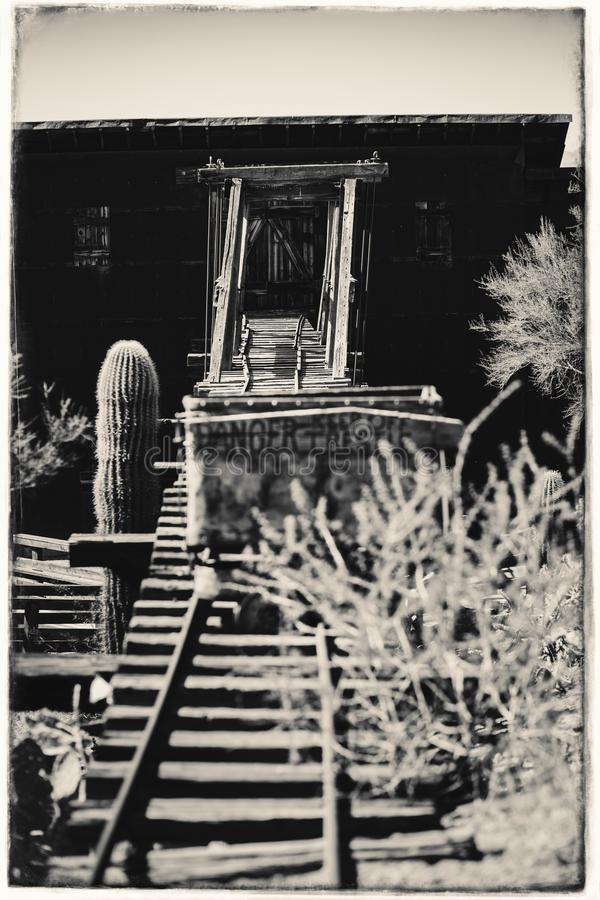 Schwarzweiss-Sepia-Weinlese-Foto des alten gefährlichen Eingangs der Goldvorkommen-Goldmine zu einem Goldminenschacht mit Laufkat stockfotos