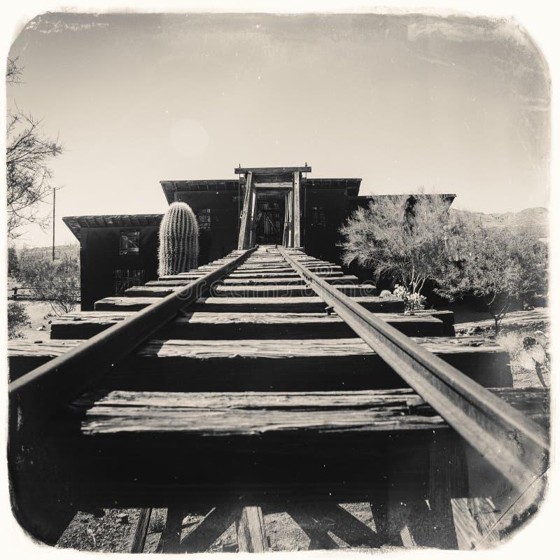 Schwarzweiss-Sepia-Weinlese-Foto des alten gefährlichen Eingangs der Goldvorkommen-Goldmine zu einem Goldminenschacht mit Laufkat lizenzfreies stockfoto
