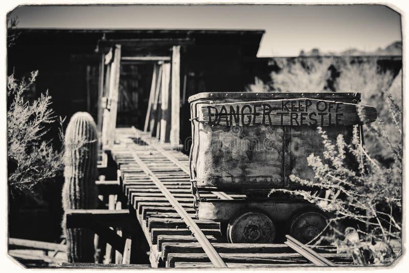 Schwarzweiss-Sepia-Weinlese-Foto des alten gefährlichen Eingangs der Goldvorkommen-Goldmine zu einem Goldminenschacht mit Laufkat lizenzfreies stockbild