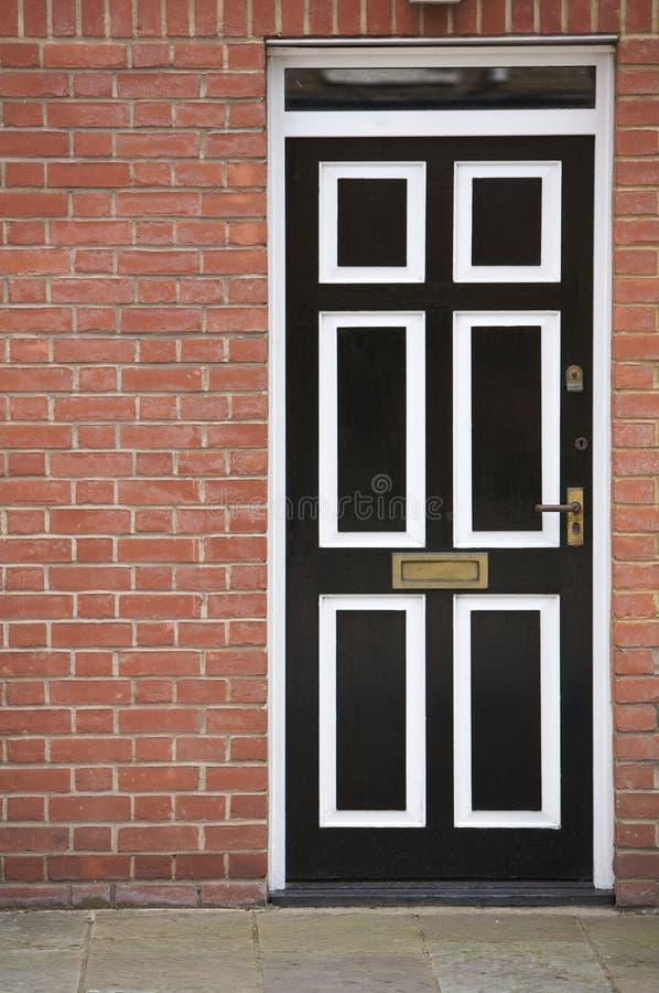Schwarzweiss-Tür mit einer Backsteinmauer stockfoto