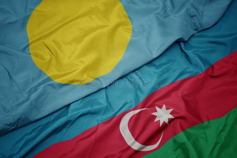 schwebende farbenfrohe Flagge von Azerbaijan und nationale Flagge von Palau lizenzfreie stockfotos
