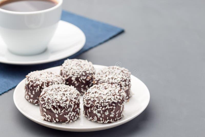 Schwedische Bonbonschokoladenb?lle oder chokladbollar, gemacht von den Hafern, Kakao, Butter und Kokosnuss, auf der wei?en Platte stockfotos