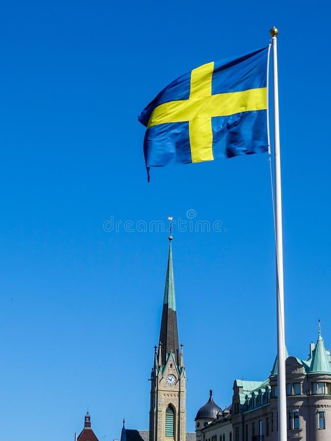 Schwedische Flagge mit einer Kirche im Hintergrund lizenzfreie stockfotos