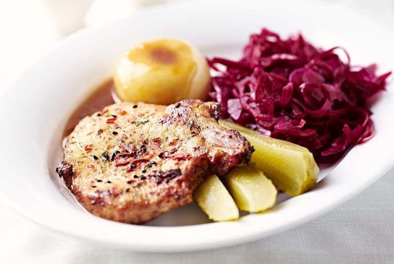 Schweinebratenhieb mit Kartoffelmehlklößen und Rotkohl stockfotos