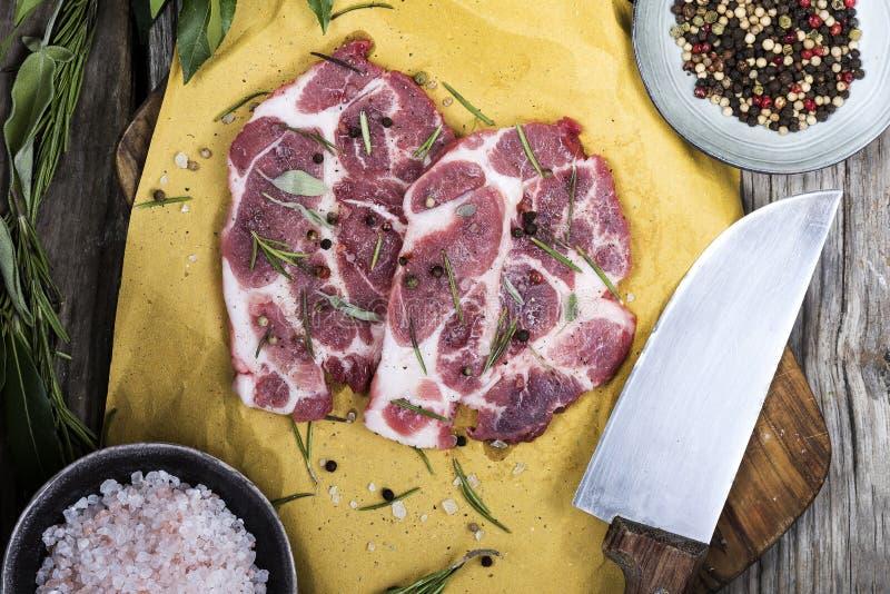 Schweinefleisch auf hackendem Brett mit Gewürzen lizenzfreie stockbilder