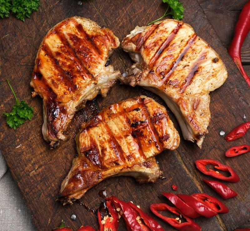 Schweinefleisch briet Steak auf der Rippe liegt auf einem hölzernen Brett des Weinlesebrauns stockfotografie