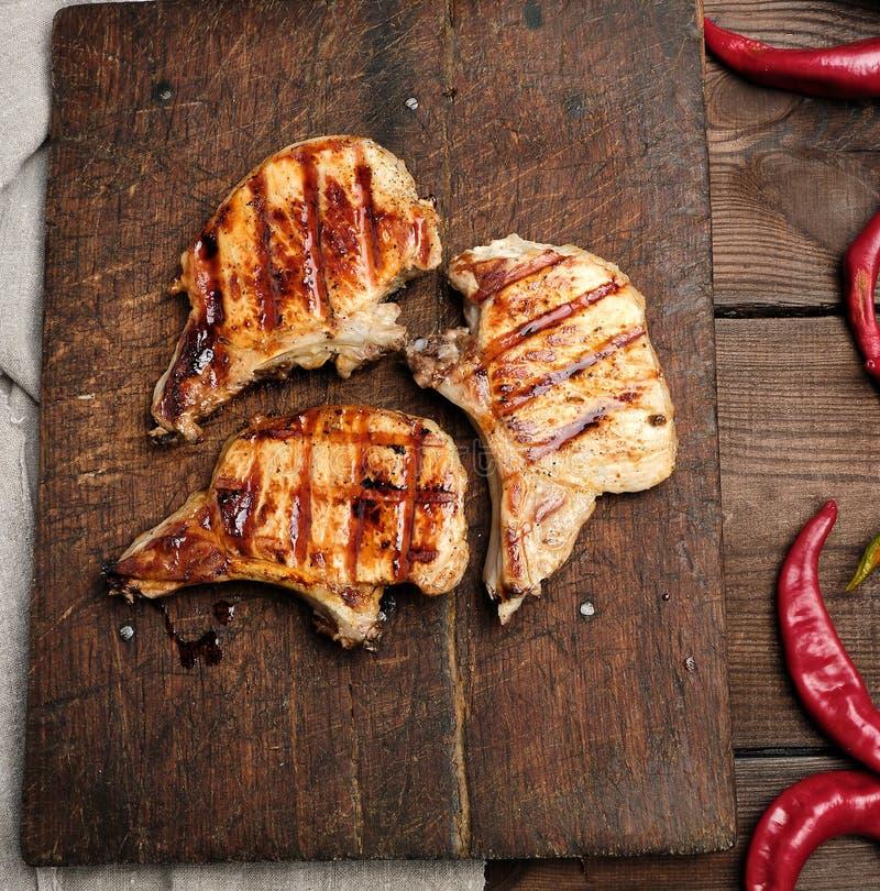 Schweinefleisch briet Steak auf der Rippe liegt auf einem hölzernen Brett des Weinlesebrauns lizenzfreie stockfotografie