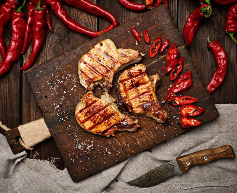 Schweinefleisch briet Steak auf der Rippe liegt auf einem hölzernen Brett des Weinlesebrauns stockbilder