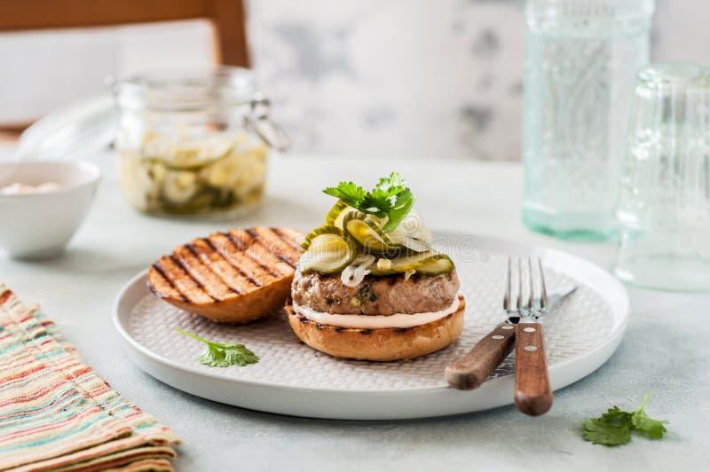 Schweinefleisch-Burger mit frischen Essiggurken lizenzfreies stockfoto