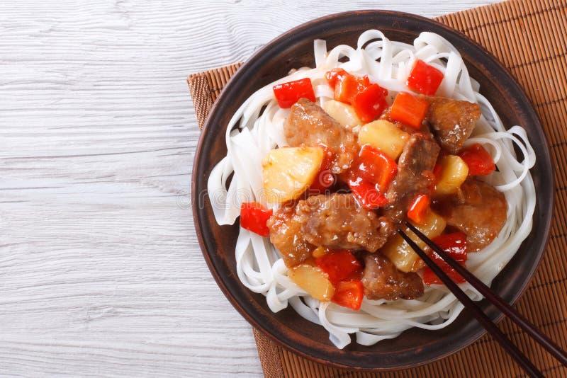 Schweinefleisch in der süß-sauren Soße mit Draufsicht der Reisnudeln lizenzfreie stockfotos