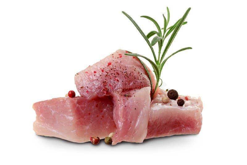 Schweinefleisch- oder Rindfleischstücke des rohen Fleisches mit Rosmarinzweig und Gewürze lokalisiert auf weißem Hintergrund lizenzfreie stockfotografie