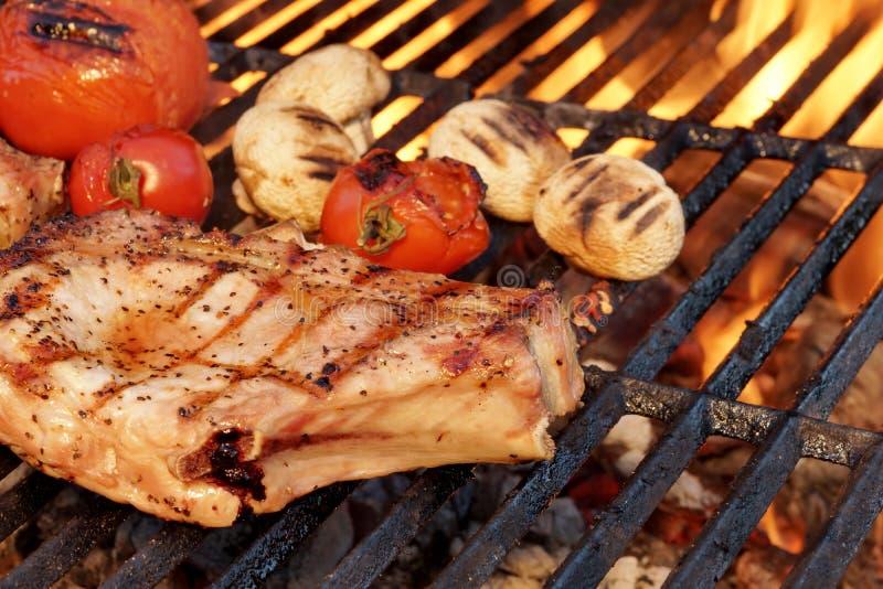 Schweinefleisch Rib Steak, Tomate und Pilze auf heißem BBQ-Grill lizenzfreie stockfotos