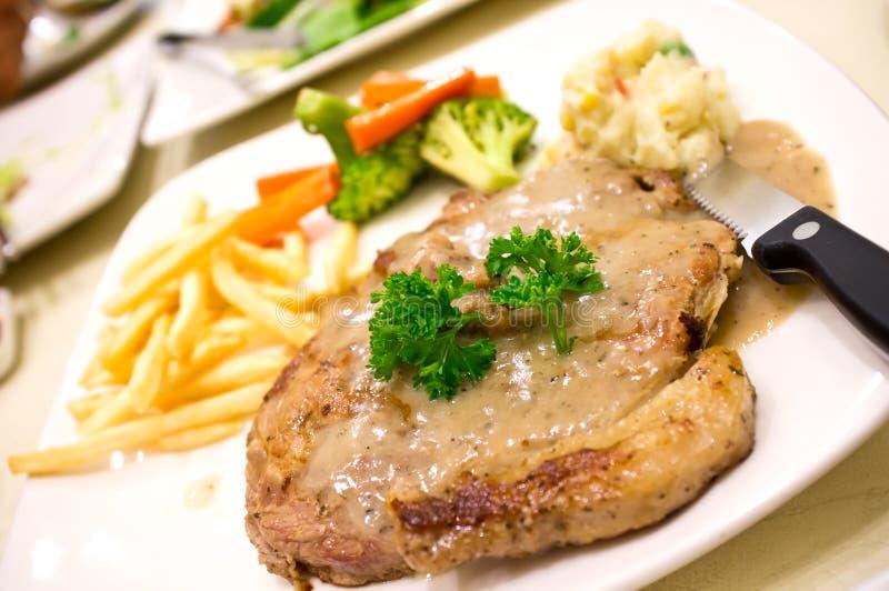 Schweinefleisch-Steak mit Pfeffer Creame Soße auf weißem Teller lizenzfreie stockbilder