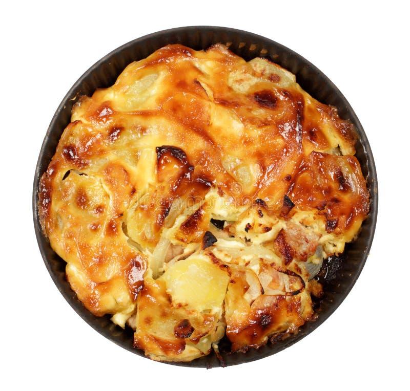 Schweinefleisch unter einer Schicht Kartoffeln, Zwiebeln und Mayonnaise im heißen Teller stockfoto