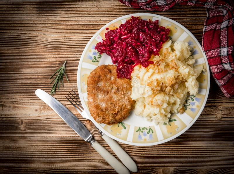 Schweinefleischkotelett mit Hackfleisch diente mit gekochten Kartoffeln und Biene stockfoto
