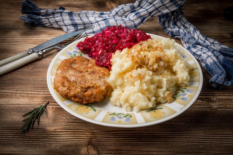 Schweinefleischkotelett mit Hackfleisch diente mit gekochten Kartoffeln und Biene lizenzfreies stockfoto